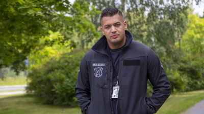 """En man iklädd en jacka som det står """"security"""" på. I bakgrunden syns träd med gröna löv."""