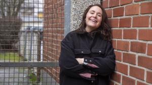 En kvinna med långt hår står lutad mot en tegelvägg.