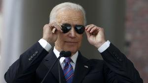 Biden tar på sina solglasögon vid en tillställning på Harvard.
