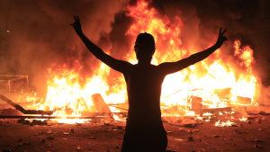 Tumma hahmo tulipaloa vasten.