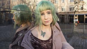 Henna Johansdottar sitter på marken lutad mot en glasvägg medan hon tittar rakt in i kameran. Hennes jacka är uppknäppt och hon blottar en fjärilstatuering på sin högra axel.
