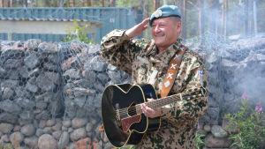 """Rauhanturvaajamies maastpupuvussa ja sinibaretissa, oikea käsi """"lipassa"""", vasen olalla roikkuvan kitaran varressa."""
