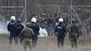 Grekiska poliser och militärer betraktar migranter på den turkiska sidan av gränsen mellan Grekland och Turkiet i Kastanies/Pazarkule.