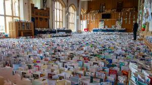 Tiotusentals födelsedagskort utlagda på golvet till aulan i en skola