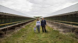 Ett barn, en kvinna och en man står mellan två långa, låga hus. Vi befinner oss på en rävfarm.