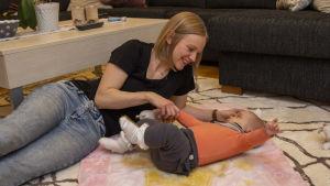 En kvinna ligger på sitt vardagsrumsgolv och leker med sin bebis.