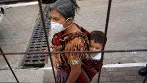 En kvinna köar för ett mål varm mat i Villa Nueva i Guatemala