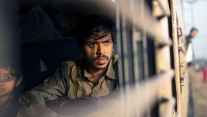 Intialainen näyttelijä Adarsh Gourav katsoo ulos junan ikkunasta elokuvassa Valkoinen tiikeri