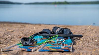 Grodfötter, snorkel och annan dykutrustning på en sandstrand.