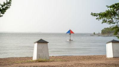 Simhus, strand, hav och en karusell i vattnet.