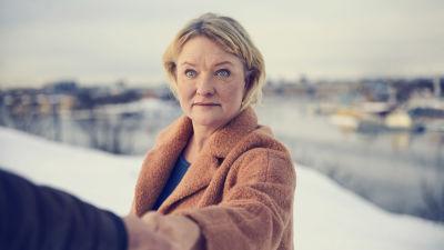 En blond dam i ett vintrigt landskap håller någons hand i förgrunden.