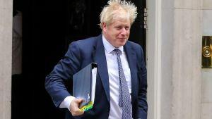 Britannian pääministeri Boris Johnson poistuu työasunnoltaan parlamentin kyselytunnille 23. lokakuuta 2019. Johnsonilla on kädessään kansio, jossa on useita eri värikoodilappuja.