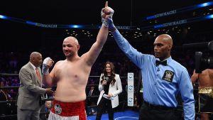Domaren håller upp Adam Kownackis vänstra arm för att signalera att han vunnit en match