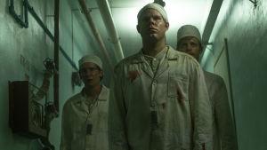 Miehet kävelevät Tsernobylin ydinvoimalan käytävällä televisiosarjassa Chernobyl.