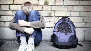 En ensam pojke sitter lutad mot en vägg med huvudet mot knäna.