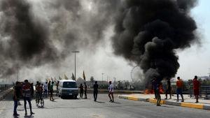 Demonstranter bränner bildäck i östra Bagdad