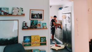 En pappa står i köket med baby i bärsele.
