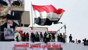 Irakiska demonstranter håller irakiska flaggan uppe på taket på en byggnad nära Tahrir-torget i centrala Bagdad.