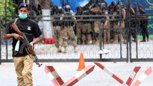 En militär bär munskydd utanför börsen i Karachi. Han håller i ett vapen. I bakgrunden ses fler militärer.