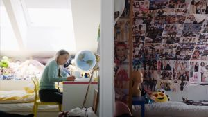 På bilden syns klimataktivisten Greta Thunberg hemma där hon sitter vid skrivbordet i sitt rum. På skrivbordet står en jordglob och en vägg är helt fylld av affisher och foton.
