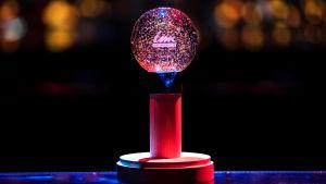 """UMK-kiertopalkinto jalustalla. Palkinto muistuttaa mikrfonia, jonka pää on """"lumipallo"""", jonka sisällä on UMK-teksti."""