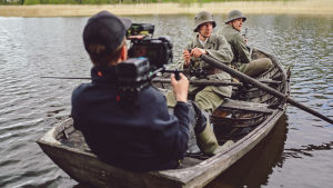 Två soldater i en gammal träeka. De är skådespelare. I båten sitter också en person i nutida kläder med filmkamera på axeln.