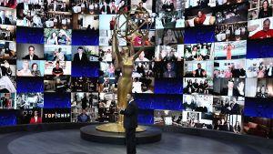 Bild på programledaren för Emmygalan. Står på en scen omringad av en skärm med massa små bilder på personer som är med live.