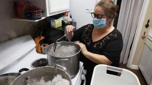 En kvinna som smälter snö i kastruller på spisen.