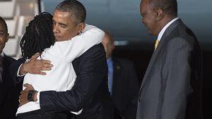Obama möts av sin halvsyster Auma Obama och president Uhuru Kenyatta på Nairobis flygfält, Kenya.