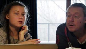 På bilden syns Greta och pappa Svante Thunberg. De sitter vid ett bord med en dator framför sig och pratar.
