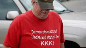 """Man med t-tröja med texten: """"Demokraterna förslavade de svarta och startade Ku Klux Klan""""."""