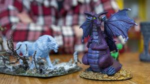 Miniatyrmodeller i plast som föreställer en vit varg och en lila drake.