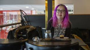 En kvinna med rosa hår. Hon sitter vid ett bord i ett kafé. Framför sig har hon en kaffe och en kakbit.