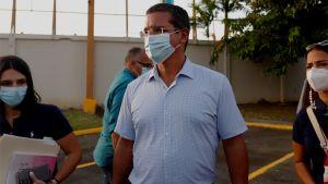 Puertoricanske politikern Pedro Pierluisi i vit pikéskjorta och ansiktsmask.