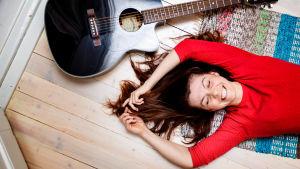 Susanne Marins på golvet med en gitarr.
