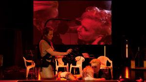 Två skådespelare sitter på scengolvet, en kvinna med en videokamera filmar dem och närbilden på deras ansikten projiceras på en duk i bakgrunden.