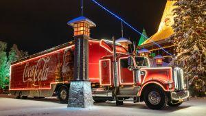 Coco-Colan valaistu joulurekka pysäköitynä napapiirillä joupukin pajan edessä.