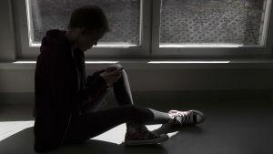 En ung person sitter på ett fönsterbräde och tittar ner på sin telefon.