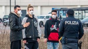 En polis står och pratar med personer i Italien som bär munskydd till följd av coronaviruset.