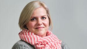 En blond kvinna med orange och vitrandig scarves. Grå tröja. Officiell porträttbild