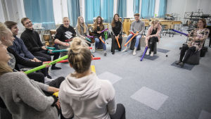 Opettajaopiskelijat istuvat puolikaaressa värikkäiden soittimien kanssa.