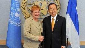 En kvinna och en man skakar hand framför en FN-logo.