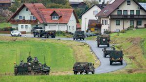 Militärfordon kör på en slingrig väg i gröna landskap.