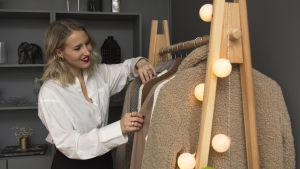 En kvinna med blont hår, iklädd en vit skjorta och svarta byxor, står invid en klädställning och tittar på kläderna som hänger på den.