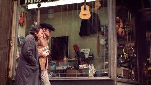 Ratso Rizzo (Dustin Hoffman) ja Joe Buck (Jon Voight) kävelevät panttilainaamon näyteikkunan ohi elokuvassa Keskiyön cowboy.