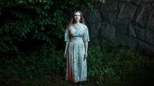 Nainen seisoo kallion ja puun edessä ja katsoo kameraan