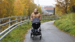En blond kvinna iklädd en tjock beige dunjacka. Hon går på en trottoar med en barnvagn. I bakgrunden syns träd med gula höstlöv.