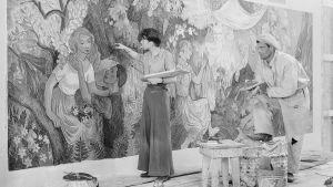 Svartvit bilid på Tove Jansson när hon måla fresken Fest på landet