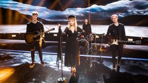 Haloo Helsinki! -yhtye poseeraa vakavailmeisenä mustiin pukeutuneena UMK-lavalla. Ellillä hautajaisasua muistuttava pillerihattu ja musta huntu.