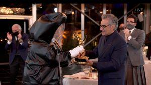 Eugene Levy tar emot sin Emmystatyett av en prisutdelare som klätt in i en heltäckande kostym för att minimera smittorisk för coronaviruset.